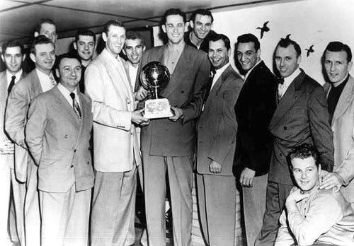 The Minneapolis Lakers hold the championship trophy.