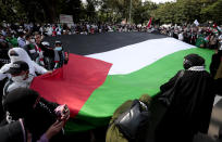 Protesters display a large Palestinian flag during a rally condemning Israeli attacks on the Palestinians, outside the U.S. Embassy in Jakarta, Indonesia, Tuesday, May 18, 2021. Pro-Palestinian protesters marched to the heavily guarded embassy on Tuesday to demand an end to Israeli airstrikes in the Gaza Strip. (AP Photo/Dita Alangkara)