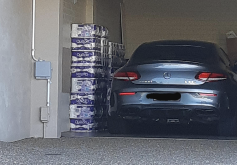 A Mercedes parked in a garage next to stacks of toilet paper.