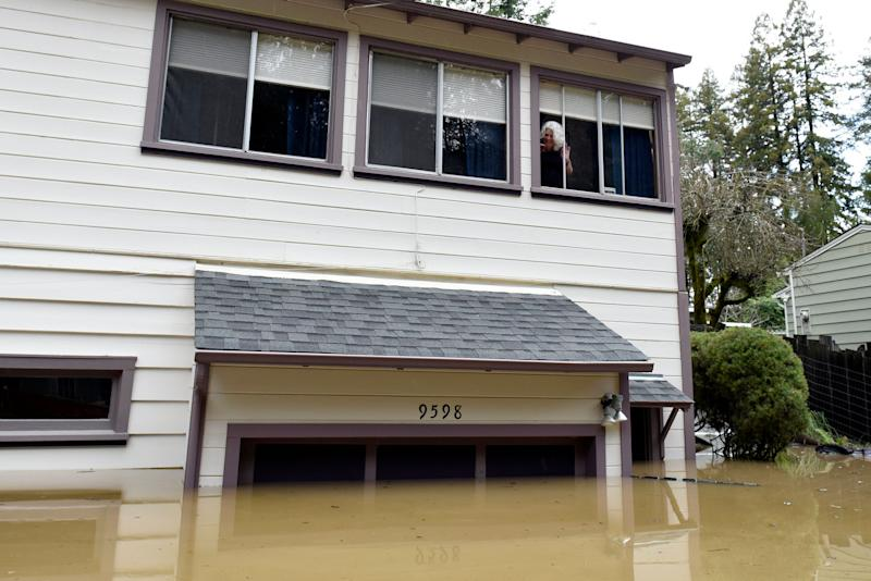 Cheryl Hughes looks out of her window of her home that is surrounded by flood waters of the Russian River in Forestville, Calif., on Feb. 27, 2019. (Photo: Michael Short/AP)