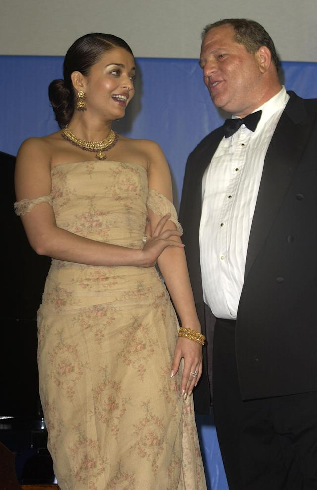 "Aishwarya Rai stands next to Harvey Weinstein while being watched like a hawk by her manager, Simone Sheffield, at the 2003 Cannes Film Festival. Rai's opting not to wear a dress designed by Weinstein's then-girlfriend, Georgina Chapman, during the festival led to a nasty exchange of words between a ""ballistic"" Weinstein and Sheffield. (Photo: J. Vespa/WireImage)"