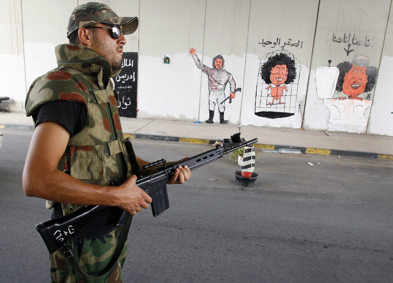 """A Libyan rebel mans a check point next to graffiti depicting ousted Moammar Gadhafi with """"I Am Here"""" written in Arabic seen on a wall inTripoli, Libya, Monday, Sept. 5, 2011. Negotiations over the surrender of one of Moammar Gadhafi's remaining strongholds have collapsed, and Libyan rebels were waiting for orders to launch their final attack on the besieged town of Bani Walid, a spokesman said. (AP Photo/Francois Mori)"""