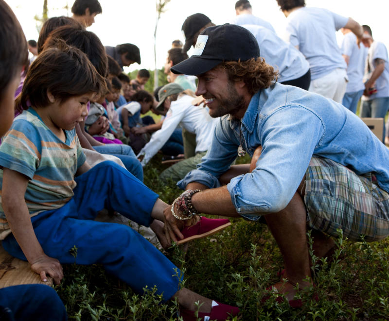 This September 2010 photo shows Blake Mycoskie, founder of TOMS Shoes, in the Misiones provinces of Argentina, giving away the 1 millionth pair of donated shoes as part of his one-for-one model – for every pair of shoes a customer buys, a pair is donated to a child in need. In a world where fashion and charity are usually associated with glitzy high-society events, a shoe company has proven that anyone can help save the world _ one pair of funky canvas shoes at a time.      (AP Photo/Toms Shoes)  NO SALES