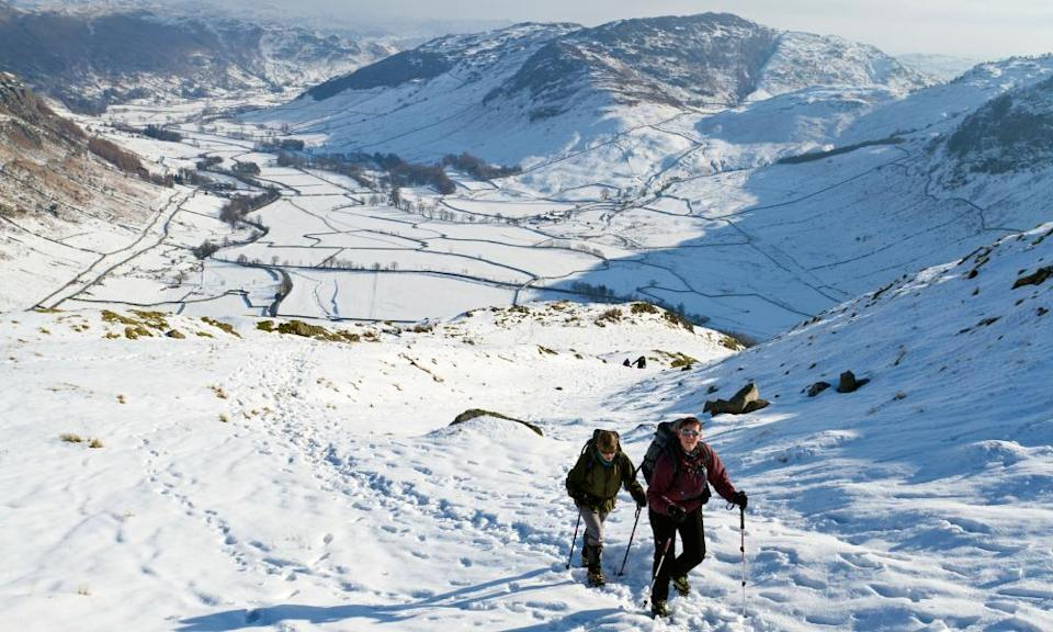 Two hikers looking down to Great Langdale in winter conditions.