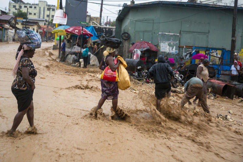 Street vendors cross a flooded street during Tropical Storm Laura in Port-au-Prince, Haiti, Sunday, Aug. 23, 2020. Tropical Storm Laura battered the Dominican Republic and Haiti and heading for a possible hit on the Louisiana coast as a hurricane, along with Tropical Storm Marco. (AP Photo/Dieu Nalio Chery)