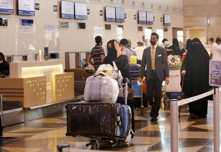 Saudi passengers prepare to check-in for flights at the King Abdulaziz International Airport in Jiddah, Saudi Arabia, Monday, May 17, 2021. Vaccinated Saudis will be allowed to leave the kingdom for the first time in more than a year as the country eases a ban on international travel that had been in place to try and contain the spread of the coronavirus and its new variants. (AP Photo/Amr Nabil)