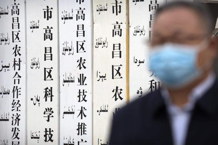 """A government official stands near a sign board outside a location that was identified in early 2020 as a re-education facility by an Australian think tank, which the Chinese government asserts is currently home to a veterans' affairs bureau and other offices, in Turpan in western China's Xinjiang Uyghur Autonomous Region during a government organized trip for foreign journalists, Thursday, April 22, 2021. A spokesperson for the Xinjiang region called accusations of genocide """"totally groundless"""" as the British parliament approved a motion Thursday that said China's policies amounted to genocide and crimes against humanity. (AP Photo/Mark Schiefelbein)"""
