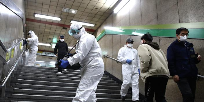 Workers in protective gear spray an anti-septic solution to fight the coronavirus in a subway station in Seoul, South Korea, on February 21, 2020.