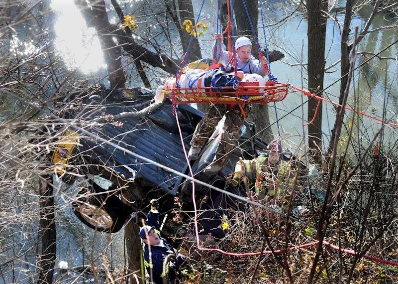 Firefighters and rescue workers lift 33-year-old Erin Dawn Bowser who was conscious and talking to rescuers as they retrieved her with ropes and ladders from her smashed  pick up truck that landed in the trees above the Connoquenessing Creek on Route 68 near Evans City, Pa in Butler County on Monday Nov. 29, 2010.  Police believe the woman's truck flew over the guardrail and landed in the branches of the trees about 30 feet below the road. Police say they'll be citing Bowser for driving too fast for conditions. (AP Photo/Pittsburgh Post-Gazette, Robin Rombach) NO SALES