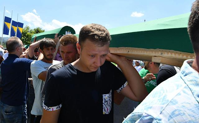 <p>Bosnian Muslims, survivors of Srebrenica 1995 massacre, as well as other visitors, carry one of many caskets containing the remains of their relatives, before final burial at memorial cemetery in village of Potocari, near the eastern Bosnian town of Srebrenica, on July 11, 2017. (Photo: Elvis Barukcic/AFP/Getty Images) </p>