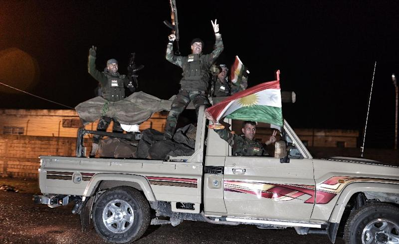 Kurdish peshmerga fighters wave a Kurdish flag from a military vehicle armed with a heavy infantry weapons as they ride towards the Syrian town of Kobane from the border town of Suruc, Turkey, October 31, 2014 (AFP Photo/)