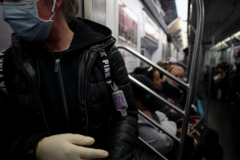 NEW YORK, USA - MARCH 11: A woman wears a face mask, surgical gloves and a hand sanitizer attached herself to prevent Covid-19 spread, at the New York City subway train in New York, United States on March 11, 2020. (Photo by Tayfun Coskun/Anadolu Agency via Getty Images)