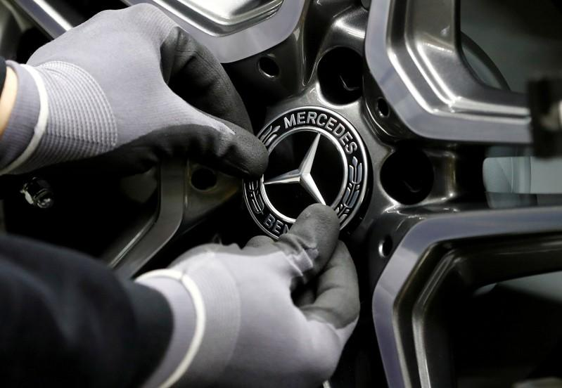 FILE PHOTO: An employee of German car manufacturer Mercedes Benz installs a hubcap at a A-class model at the production line at the Daimler factory in Rastatt