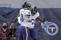 Baltimore Ravens quarterback Lamar Jackson (8) celebrates with running back Justice Hill after Jackson scored a touchdown on a 48-yard run against the Tennessee Titans in the first half of an NFL wild-card playoff football game Sunday, Jan. 10, 2021, in Nashville, Tenn. (AP Photo/Mark Zaleski)