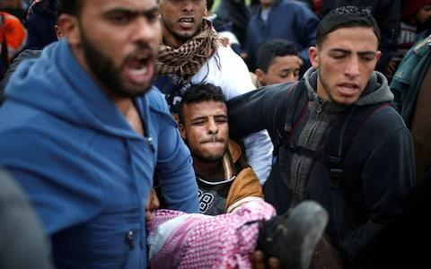 A wounded Palestinian is evacuated during clashes ahead of a major protet along the srael border with Gaza - Credit: MOHAMMED SALEM/REUTERS