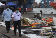 Indonesian National Transportation Safety Committee (KNKT) investigators walk near debris found in the waters around the location where a Sriwijaya Air passenger jet crashed, at the search and rescue command center at Tanjung Priok Port in Jakarta, Indonesia, Indonesia, Wednesday, Jan. 13, 2021. Divers looking for the crashed plane's cockpit voice recorder were searching in mud and plane debris on the seabed between Indonesian islands Wednesday to retrieve information key to learning why the Sriwijaya Air jet nosedived into the water over the weekend. (AP Photo/Achmad Ibrahim)