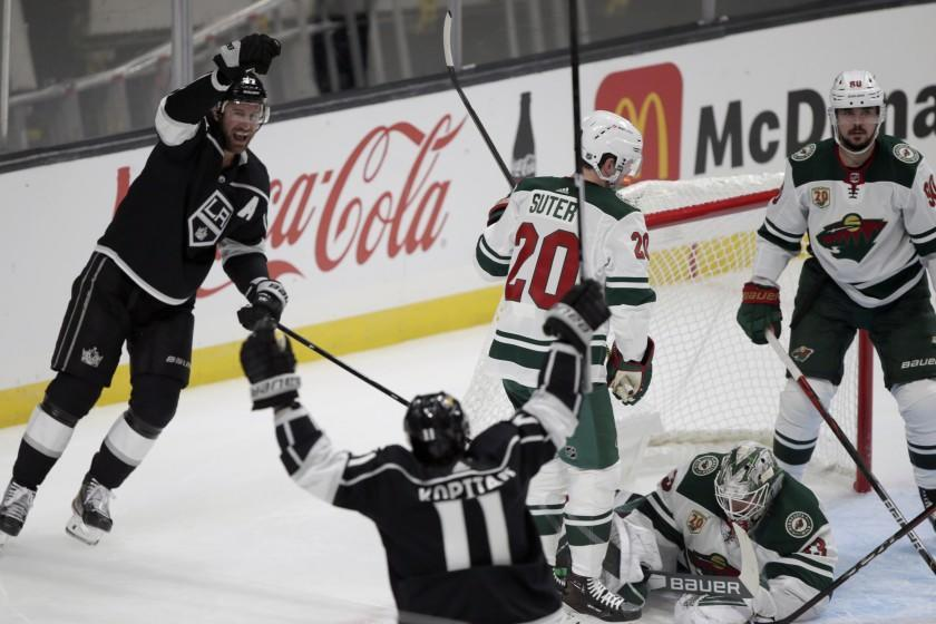 Los Angeles Kings center Jeff Carter, left, celebrates his goal with center Anze Kopitar, second from left, of Solvania, against Minnesota Wild goaltender Cam Talbot, second from right, defenseman Ryan Suter, center, and center Marcus Johansson, right, of Sweden, during the first period of an NHL hockey game in Los Angeles, Thursday, Jan. 14, 2021. (AP Photo/Alex Gallardo)