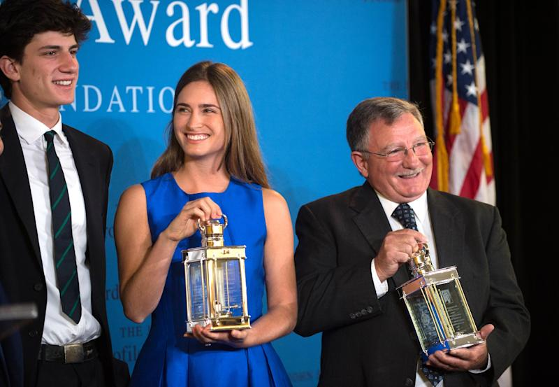 Accepting the 2014 John F. Kennedy Profile in Courage Award on behalf of her grandfather former President George H.W. Bush, Lauren Bush Lauren, center, and fellow Award recipient Paul W. Bridges, the former mayor of Uvalda, Ga, right, hold the awards as they stand with Jack Schlossberg, left, grandson of President John F. Kennedy, during a ceremony at the John F. Kennedy Library and Museum, Sunday, May 4, 2014, in Boston. (AP Photo/Gretchen Ertl)