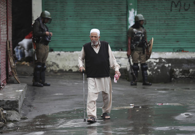 An elderly Kashmiri man crosses a road as Indian paramilitary soldiers stand guard in Srinagar, Indian controlled Kashmir, Saturday, Aug. 10, 2019. Authorities enforcing a strict curfew in Indian-administered Kashmir will bring in trucks of essential supplies for an Islamic festival next week, as the divided Himalayan region remained in a lockdown following India's decision to strip it of its constitutional autonomy. The indefinite 24-hour curfew was briefly eased on Friday for weekly Muslim prayers in some parts of Srinagar, the region's main city, but thousands of residents are still forced to stay indoors with shops and most health clinics closed. All communications and the internet remain cut off. (AP Photo/Mukhtar Khan)