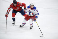 New York Rangers defenseman Ryan Lindgren (55) skates with the puck past Washington Capitals left wing Jakub Vrana (13) during the second period of an NHL hockey game, Sunday, March 28, 2021, in Washington. (AP Photo/Nick Wass)