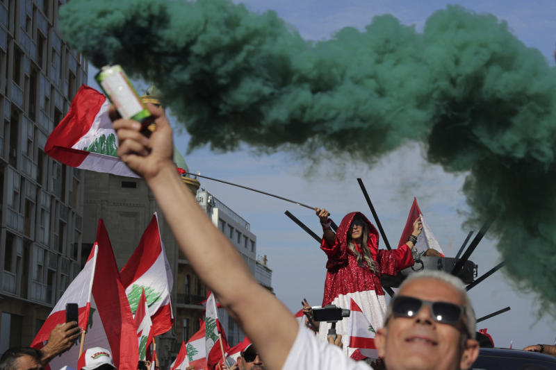 Anti-government protesters wave Lebanese national flags as hold smoke flares during separate civil parade at the Martyr square, in downtown Beirut, Lebanon, Friday, Nov. 22, 2019.  Protesters gathered for alternative independence celebrations, converging by early afternoon on Martyrs' Square in central Beirut, which used to be the traditional location of the official parade. Protesters have occupied the area, closing it off to traffic since mid-October. (AP Photo/Hassan Ammar)