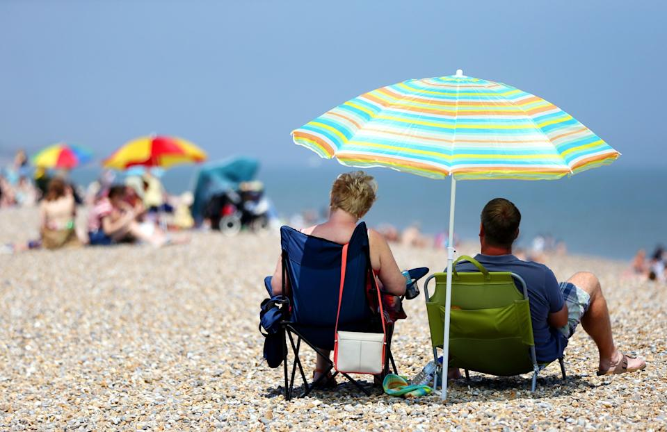 Sunbathers shelter under beach umbrellas on the seafront in Aldeburgh, Suffolk, as Britain has basked in the hottest day of the year so far, with temperatures expected to soar as the heatwave continues into next week.