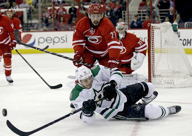 Dallas Stars' Tyler Seguin (91) falls to the ice while chasing the puck against Carolina Hurricanes' Justin Faulk (27) during the first period of an NHL hockey game in Raleigh, N.C., Thursday, April 3, 2014. (AP Photo/Gerry Broome)