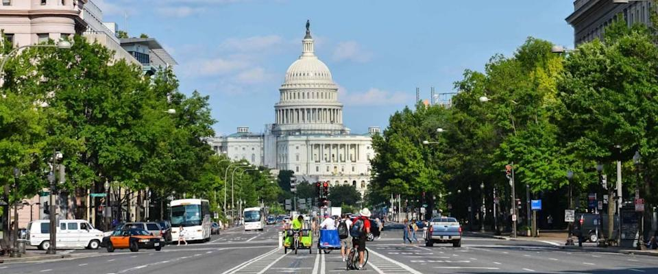 US Capitol building from Pennsylvania Avenue with car traffic foreground - Washington DC United States