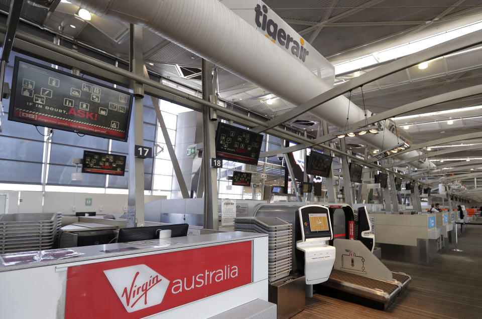 Check-in counters of Virgin Australia and Tiger Air are unattended at Sydney Airport in Sydney, Wednesday, Aug. 5, 2020. Virgin Australia will cut about 3000 jobs as the airline struggles with the effects of the coronavirus pandemic. (AP Photo/Rick Rycroft)