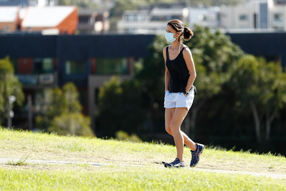 A woman walks in a Sydney park wearing a face mask. Source: AAP