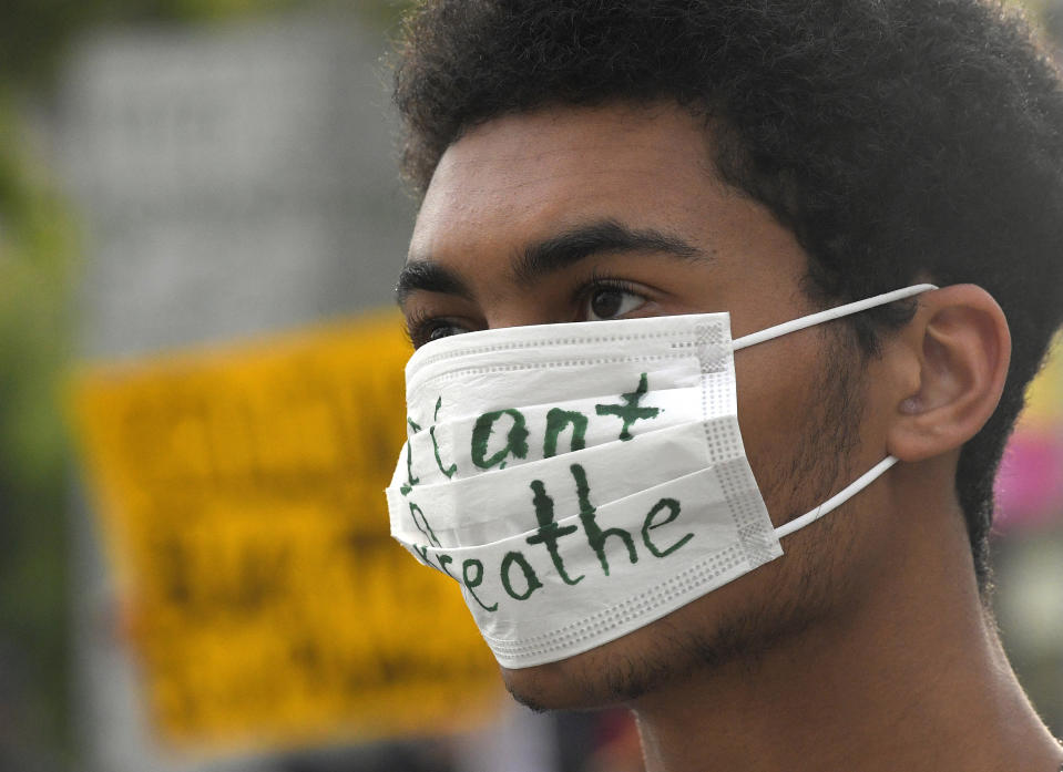 A demonstrator listens during a protest In front of Los Angeles City Hall, Tuesday, June 2, 2020, in Los Angeles over the death of George Floyd. Floyd died in police custody on Memorial Day in Minneapolis. (AP Photo/Mark J. Terrill)