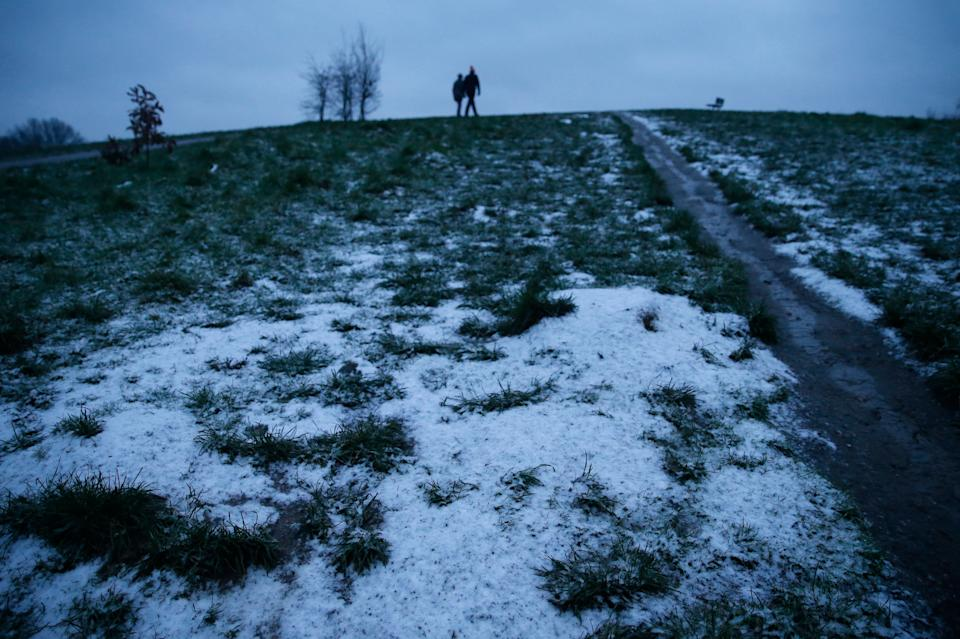 <p>People walk early morning on a partially snow covered Parliament Hill in Hampstead</p> (Getty Images)