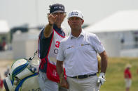 Chez Reavie, right, talks with his caddie Justin York before hitting a shot out of the rough on the 18th hole during the second round of the 3M Open golf tournament in Blaine, Minn., Friday, July 23, 2021. (AP Photo/Craig Lassig)
