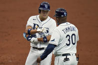 Tampa Bay Rays' Yoshi Tsutsugo, of Japan, celebrates his single off New York Yankees starting pitcher Corey Kluber with first base coach Ozzie Timmons (30) during the third inning of a baseball game Friday, April 9, 2021, in St. Petersburg, Fla. (AP Photo/Chris O'Meara)