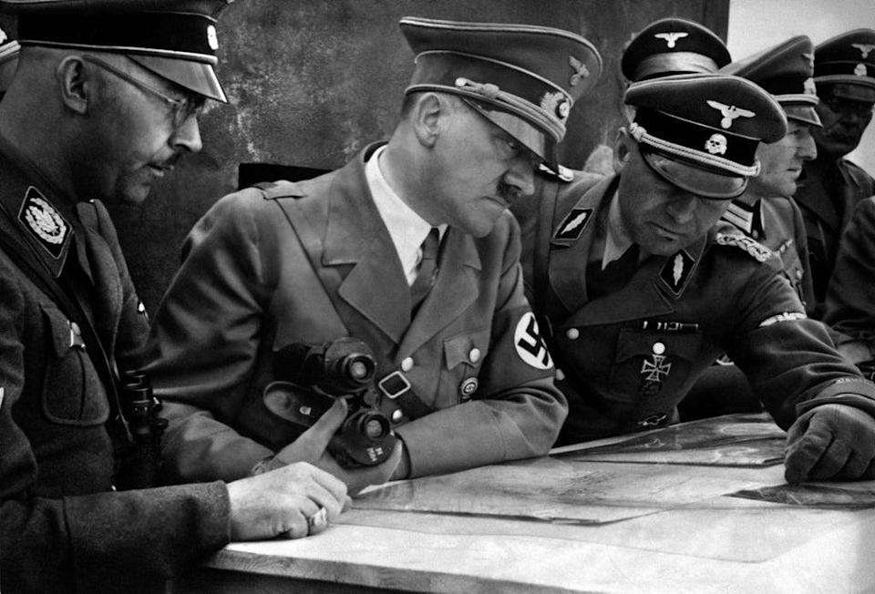 A picture dated 1939 shows German Nazi Chancellor and dictator Adolf Hitler (C) consulting a geographical survey map with his general staff including Heinrich Himmler (L) and Martin Bormann (R) at an unlocated place during World War II (AFP via Getty Images)