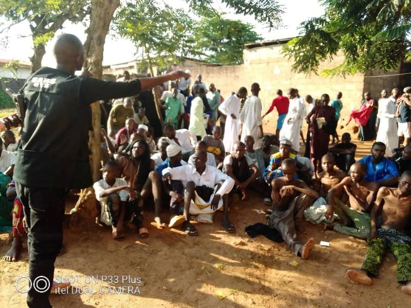 A police officer talks to people who sit on the ground after being freed by police from an Islamic rehabilitation centre in Ibadan