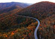 """While New England's trees get most of the attention in the fall, you should be turning south, towards the colors of the Blue Ridge Parkway and Carolina mountains. Make <a href=""""https://www.cntraveler.com/gallery/best-day-trips-from-charlotte-nc?mbid=synd_yahoo_rss"""" rel=""""nofollow noopener"""" target=""""_blank"""" data-ylk=""""slk:Asheville"""" class=""""link rapid-noclick-resp"""">Asheville</a> your home base for exploring the parkway in both directions: to the south, drive to Pisgah National Forest, filled with waterfalls and fall foliage-covered hills on view from Looking Glass Rock, and to the north, the curving Linn Cove Viaduct hugs Grandfather Mountain, offering some of the parkway's most iconic views. Shoot for mid-October to see the leaves in full color. In Asheville, make plans to eat—a lot. <a href=""""https://www.cntraveler.com/restaurants/benne-on-eagle/benne-on-eagle?mbid=synd_yahoo_rss"""" rel=""""nofollow noopener"""" target=""""_blank"""" data-ylk=""""slk:Benne on Eagle"""" class=""""link rapid-noclick-resp"""">Benne on Eagle</a> is serving up its blend of African and Appalachian influences al fresco this fall on its patio, while tapas from <a href=""""https://www.cntraveler.com/restaurants/curate-asheville/curate-asheville?mbid=synd_yahoo_rss"""" rel=""""nofollow noopener"""" target=""""_blank"""" data-ylk=""""slk:Cúrate"""" class=""""link rapid-noclick-resp"""">Cúrate</a> are now available for delivery. (Even more Spanish snacks and ingredients are available from the restaurant's bodega.) <em>—Meredith Carey</em>"""