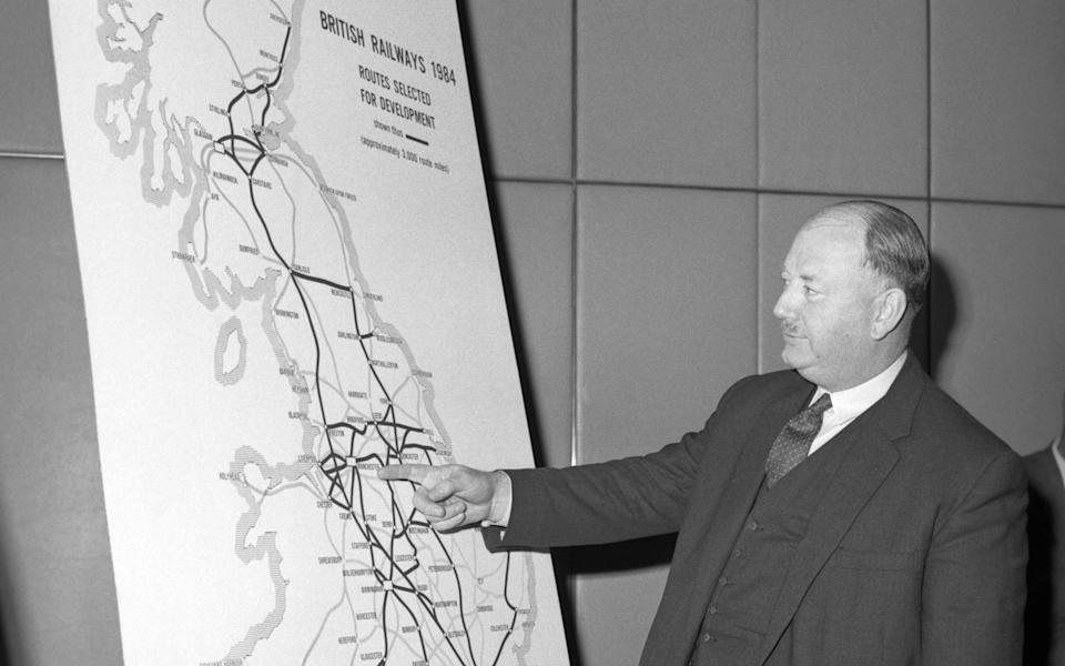 Richard Beeching looking at a large map, showing how British Rail trunk routes might look in 1984