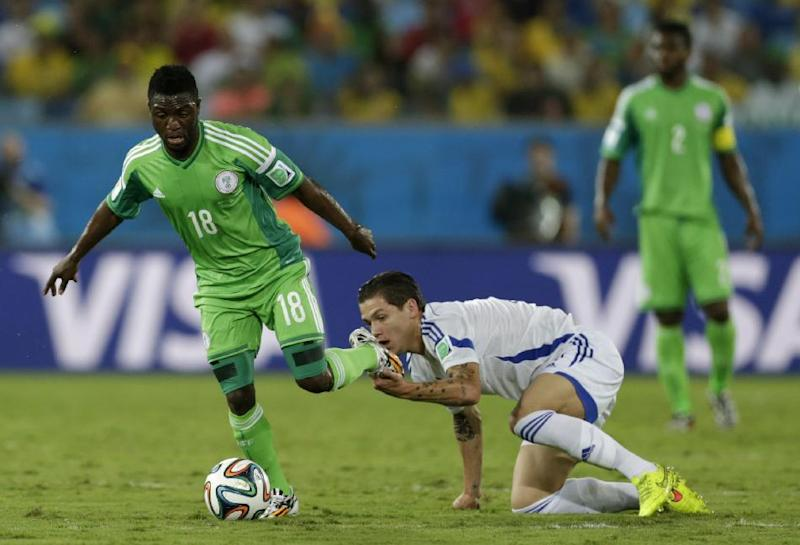 Bosnia's Muhamed Besic grabs hold of the boot of Nigeria's Michael Babatunde during the group F World Cup soccer match between Nigeria and Bosnia at the Arena Pantanal in Cuiaba, Brazil, Saturday, June 21, 2014