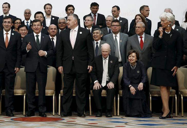 Turkey's Prime Minister Davutoglu gestures as he poses for a group photo of the G20 Finance Ministers and Central Bank Governors in Ankara