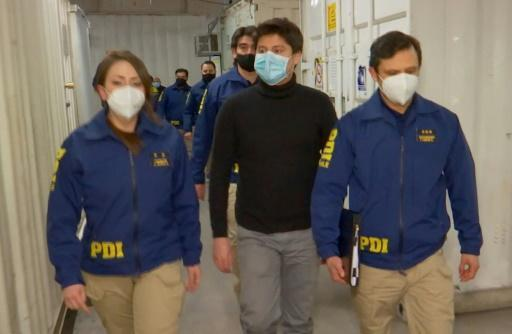 Chilean Nicolas Zepeda, centre, being escorted by police at Santiago international aiport ahead of his flight to Paris