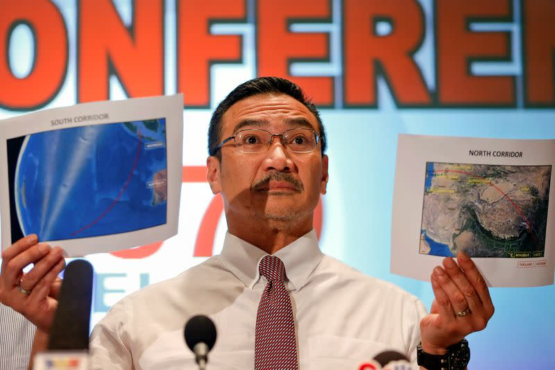 FILE PHOTO: Malaysia's acting Transport Minister Hishammuddin Hussein shows two maps with corridors of the last known possible location of the missing Malaysia Airlines MH370 plane as he addresses reporters at the Kuala Lumpur International Airport