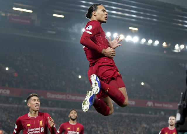 Liverpool's Virgil van Dijk jumps to celebrate scoring his side's first goal during the English Premier League soccer match between Liverpool and Manchester United at Anfield Stadium in Liverpool, Sunday, Jan. 19, 2020.(AP Photo/Jon Super)
