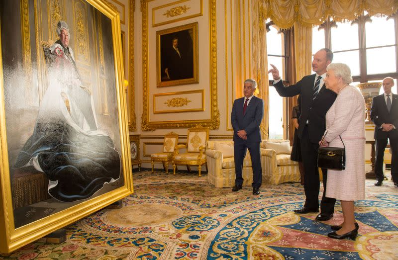 FILE PHOTO: British artist Henry Ward shows Britain's Queen Elizabeth his portrait of her, which was commissioned to mark her six decades of patronage to the British Red Cross, at Windsor Castle
