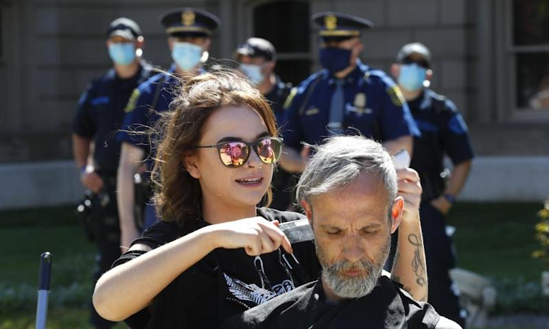 A hairstylist gives a free haircut as police watch outside the state capitol in Lansing, Michigan, on 20 May.