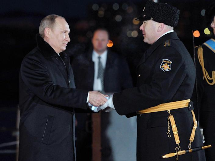 Russian President Vladimir Putin, left, hands out an the Nakhimov medal during an awarding ceremony of the crew of the Peter the Great nuclear powered cruiser to the ship captain Vladislav Malakhovsky, at a navy base in Severomorsk, Russia, on Thursday, Jan. 10, 2013. (AP Photo/RIA Novosti, Alexei Nikolsky, Presidential Press Service)