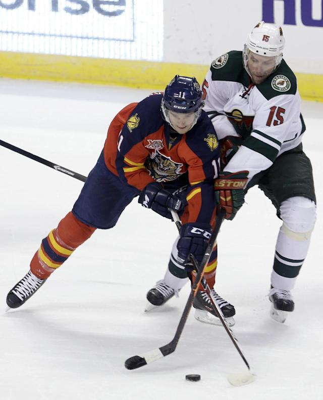 Minnesota Wild's Dany Heatley (15) battles Flprida Panthers' Jonathan Huberdeau (11) for control of the puck in the first period of an NHL hockey game on Saturday, Oct. 19, 2013, in Sunrise, Fla. (AP Photo/Alan Diaz)