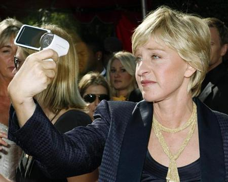 Comedian Ellen Degeneres takes her own picture as she arrives at the 59th Primetime Emmy Awards in Los Angeles, California September 16, 2007. REUTERS/Mario Anzuoni/Files