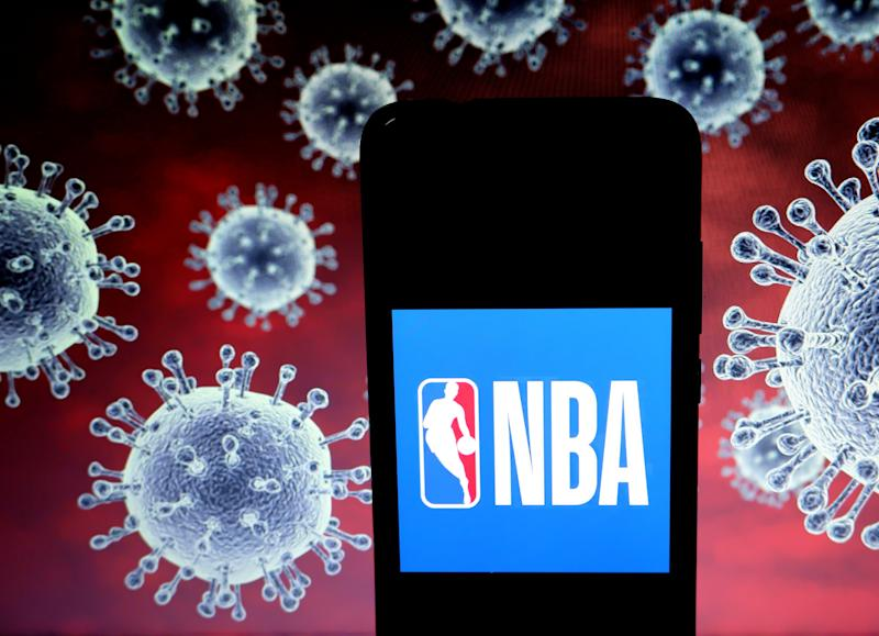 KOLKATA, INDIA - 2020/03/25: In this photo illustration a National Basketball Association (NBA) logo seen displayed on a smartphone with a computer model of the COVID-19 coronavirus in the background. (Photo Illustration by Avishek Das/SOPA Images/LightRocket via Getty Images)