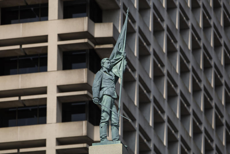 File-This June 25, 2015, file photo shows the 15-foot figure of a Confederate soldier on top of a Norfolk monument commemorating the last reunion of surviving confederate soldiers. Virginia's second largest city is suing the state in an attempt to remove an 80-foot-tall Confederate monument from its downtown. The city of Norfolk's suit was filed Monday, Aug. 19, 2019, in federal court and targets a Virginia law that prevents the removal of war memorials. (Bill Tiernan/The Virginian-Pilot via AP, File)